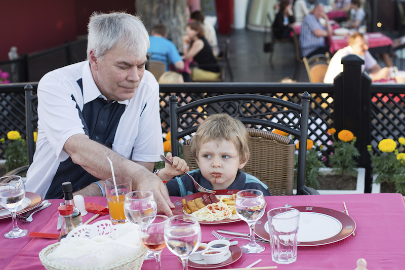 Grandfather and his grandson eating in summer restaurant
