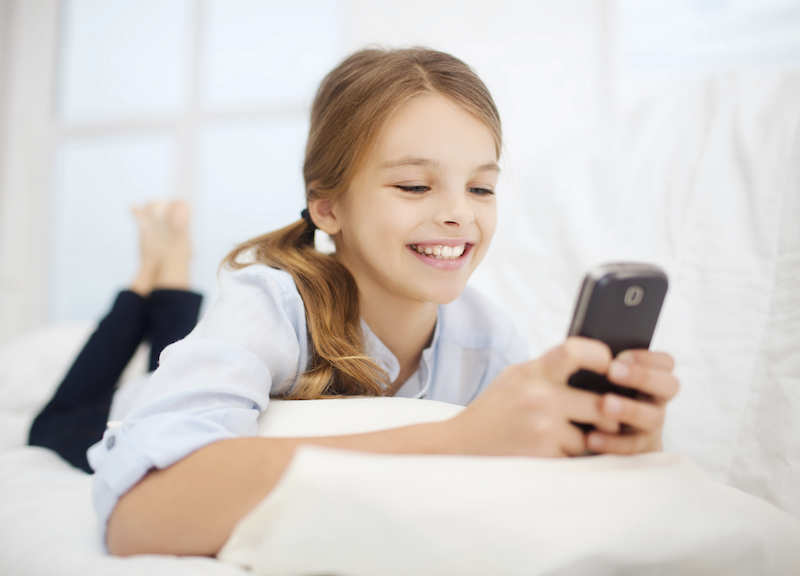 people, children, technology and internet concept - happy girl with smartphone at home