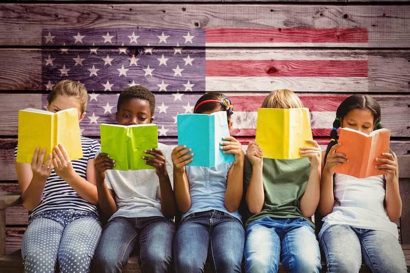 Children reading books at park against composite image of usa national flag