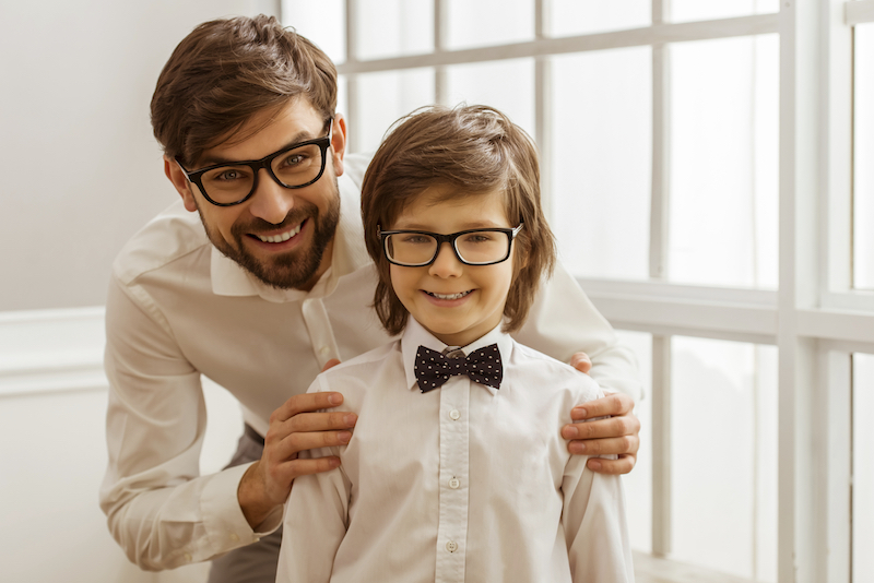 Portrait of a handsome young father and his cute little son in a bow tie. Both in white classical shirts and eyeglasses, looking in camera and smiling