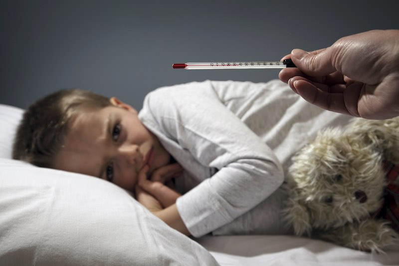 Poorly boy in bed with a thermometer reading high temperature focus on thermometer