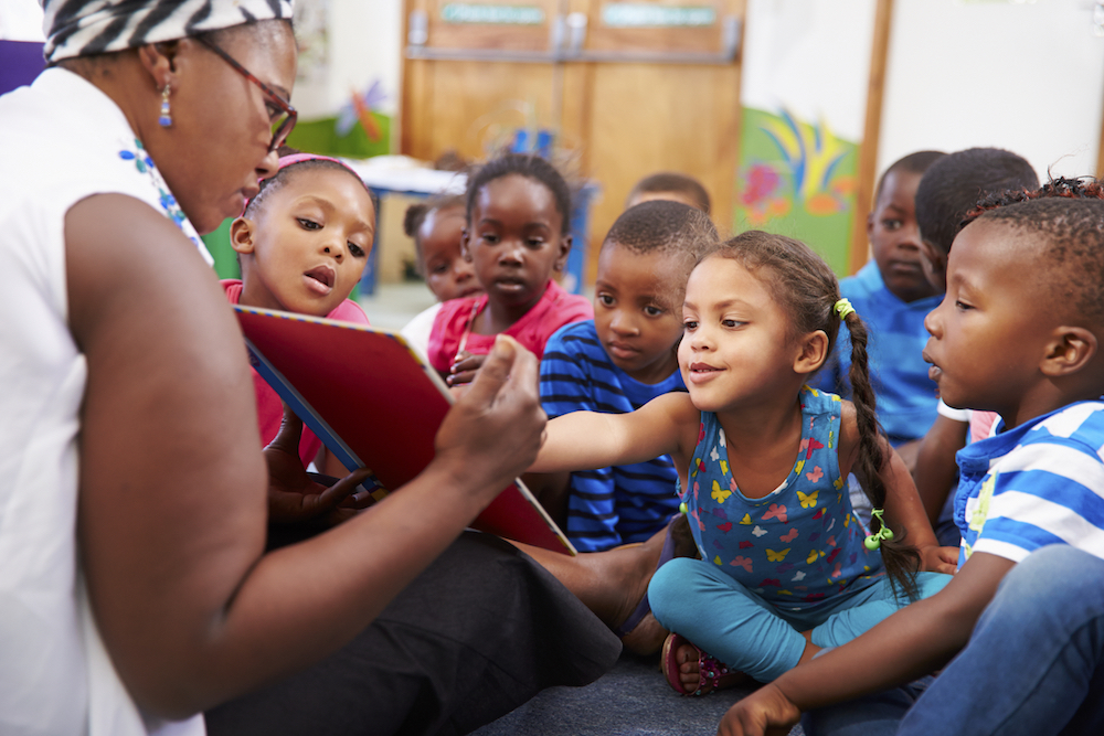 Teacher reading a book with a class of preschool children