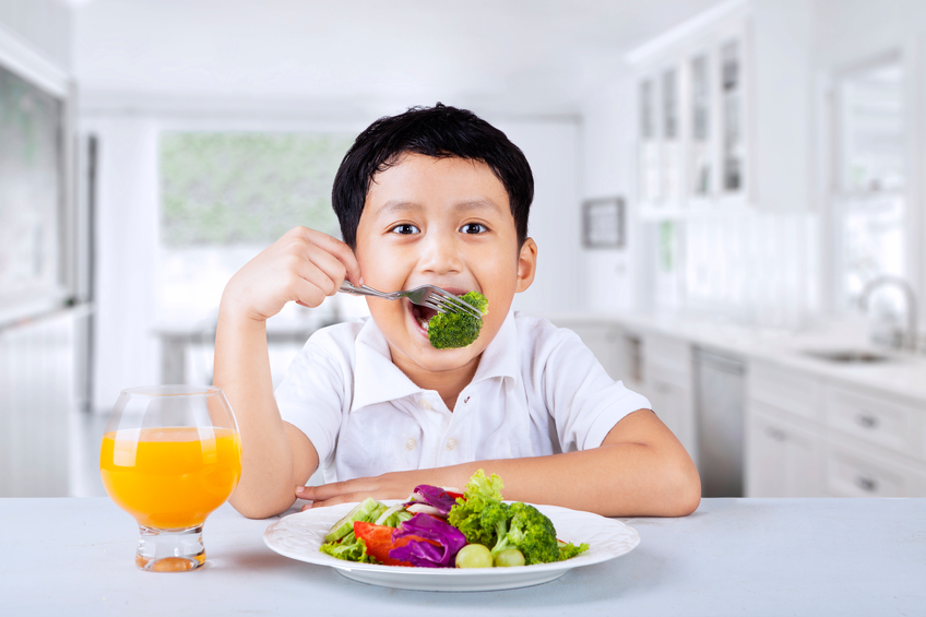 Boy eating broccoli at home