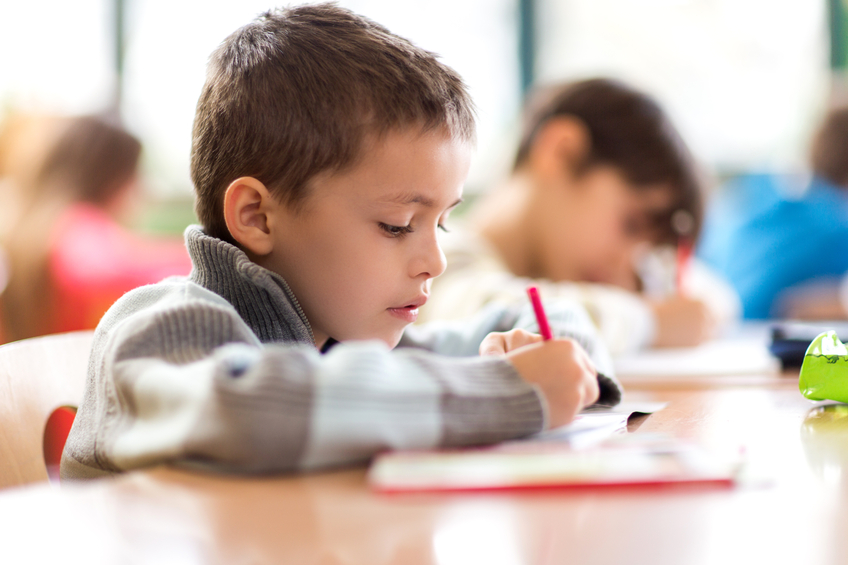 Elementary student writing in a notebook during a class.